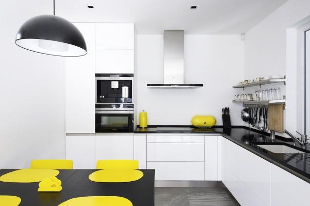 Čistá bílá plocha kuchyňské linky zvětšuje malý prostor, jasné žluté akcenty oživují neutrální šedobílou barevnost celého interiéru.