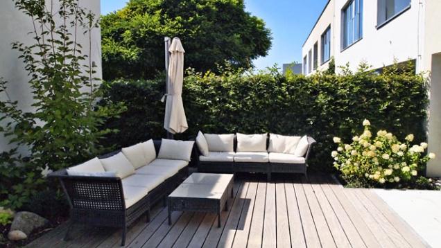 Stříhaný habrový plot sdílený se sousedy poskytuje soukromí i hezké pozadí pro ostatní výsadby. V malé zahradě ideální řešení.