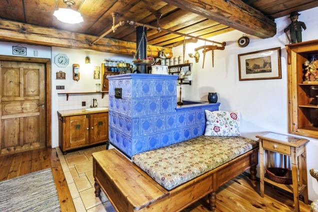 Kachlová pec slavicí (babkou) apohodlným ležením. Bylo vyrobeno ze starého dřeva.