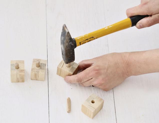 3. Do nožiček navrtáme do středu díry podle tloušťky dřevěných kolíků a do děr kápneme lepidlo. Kolíky zatlačíme do poloviny jejich výšky.