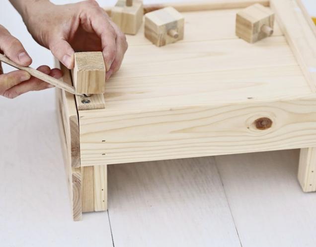 4. Nožičky postupně přikládáme na spodní stranu bedýnky a tužkou naznačíme body, kde budeme vrtat díry na uchycení druhé poloviny kolíků. Vyvrtáme díry, zakápneme lepidlem a zatlačíme nožičky s kolíky.