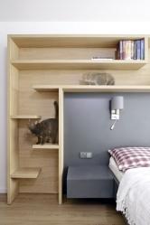Votevřených policích mají kočky své prolézačky. Našedé desce, tvořící čelo dvoulůžka jsou zavěšené noční stolky.