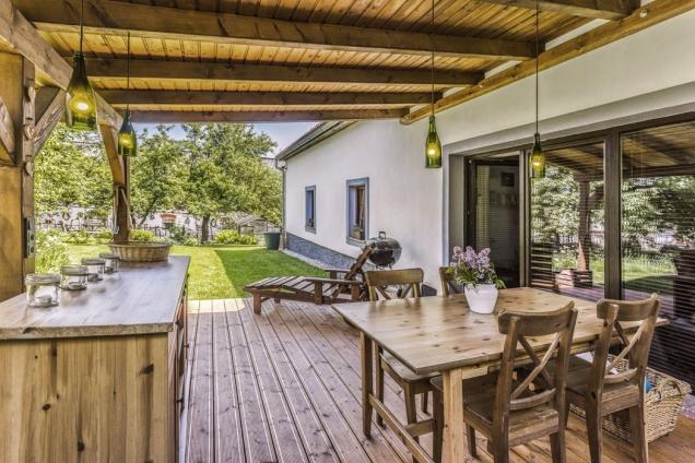 Terasa zastřešená dřevěnou pergolou je místem pro vychutnání kávy aprvním krokem dovelké přírodní zahrady.