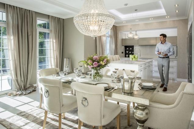 Přízemí je laděno do jemných světlých teplých tónů. Na funkcionalistickou bílou kuchyň ve vysokém lesku navazuje luxusní jídelní stůl se stříbrnou patinou a židlemi s příjemným lněným čalouněním, jejichž oblé tvary přímo vyzařují měkkost a pohodlí.