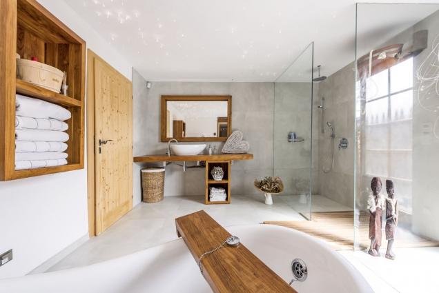 Velkoformátový obklad vodstínu světlé stěrky doplňuje nábytek adoplňky zteakového dřeva.