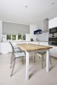 Kuchyň s jídelním stolem a pracovním pultem do L je součástí centrálního obytného prostoru v přízemí, jak to odpovídá současným trendům. Do nevelké místnosti se skvěle hodí lehké židle z čirého plastu a jemnou harmonii dotvářejí barevně sladěné textilní rolety.