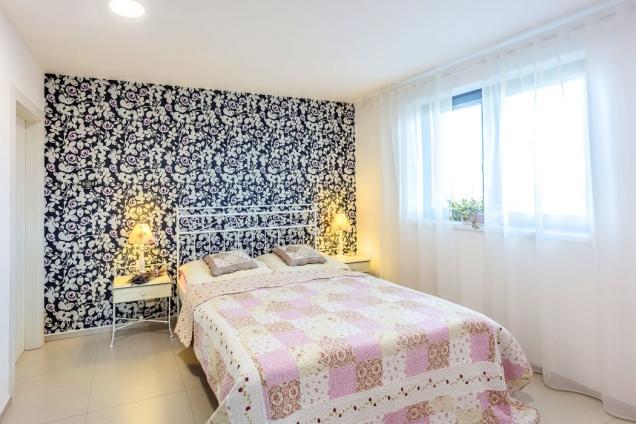 Ložnice rodičů s kovovým romantickým nábytkem a tapetou v pozadí. Na podlaze jsou sice položeny velkoformátové dlaždice, ale díky podlahovému topení nestudí.