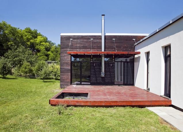 Spojením dvou částí domu vznikl prostor pro středně velkou terasu, která je krytá ze dvou stran jak před poryvy větru, tak před zraky sousedů.