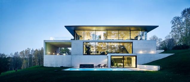 Architekti studia OUTOFBOX tomu říkají asketický design. Impozantní budova ze skla a betonu organicky zapadá do terasovitého terénu.(Zdroj: OUTOFBOX, Lotyšsko, Fotograf: Māris Ločmelis)