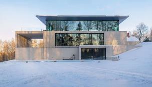 Architekti studia OUTOFBOX tomu říkají asketický design. Impozantní budova ze skla a betonu organicky zapadá do terasovitého terénu. (Zdroj: OUTOFBOX, Lotyšsko, Fotograf: Māris Ločmelis)