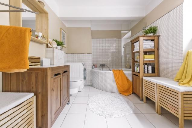 Velká koupelna srohovou vanou Rosa značky Ravak je zařízená dřevěným nábytkem zIkea.