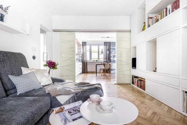 Probouráním zdi mezi dvěma místnostmi se krásně otevřel prostor mezi kuchyní aobývacím pokojem. Když je potřeba zavřít, zatáhnou se designové skleněné dveře svýplní Grafosklo.