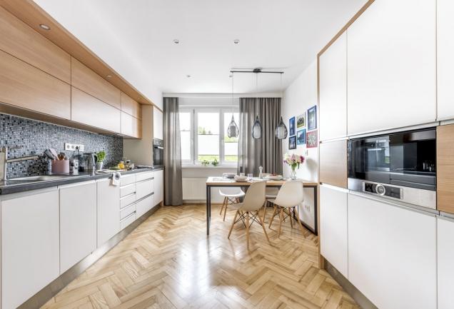 Použitím sádrokartonu nechala designérka kuchyň splynout se zdí. Levou pracovní aúložnou část doplňuje sestava skříněk smikrovlnnou troubou. Kuchyňskou sestavu ajídelní stůl vyráběl truhlář opět podle návrhu designérky.