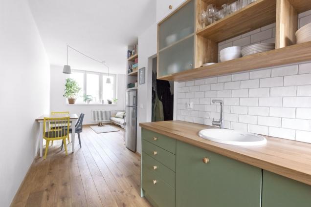 Horní část kuchyňské sestavy kombinuje otevřené police se skříňkami krytými sklem. Ustropu jsou skříňky zbílého lamina. Chladnička je umístěná vevyzděném výklenku.