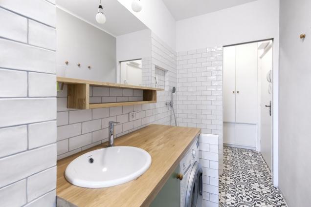 Výrazná dekorativní dlažba vynikne vjinak strohé koupelně apokračuje dále dopředsíně.