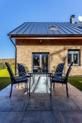 Ze zadní části domu se snadno dostanete na vydlážděnou plochu, která pokračuje až do altánu na konci pozemku.