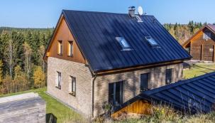 Dům je zasazen do nádherné krajiny Krušných hor, v pravém rohu obrázku vidíte střechu zahradního altánu. Střechy jsou pokryty plechovými šablonami – krytinou vhodnou na hory.