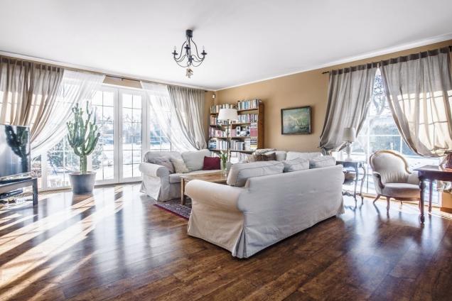 Díky množství rozměrných oken je obývací pokoj zalitý sluncem asamotný dům okna vizuálně odlehčují.