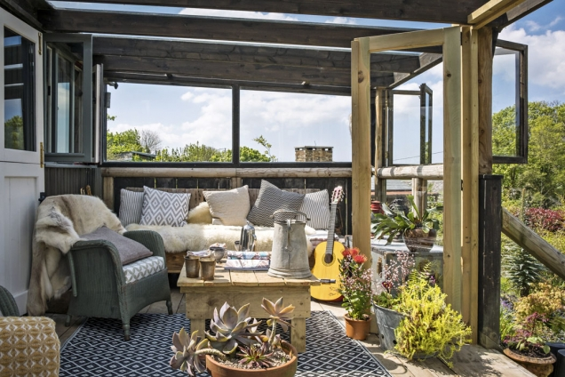 Přistavená veranda láká k posezení přes den i navečer. Originální ručně vyrobený nábytek i dekorace jsou laděné do přírodních tónů.
