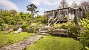 Do přímořské krajiny Cornwallu se rozhlíží maringotka přeměněná na chatu a zařízená v bohémském stylu.