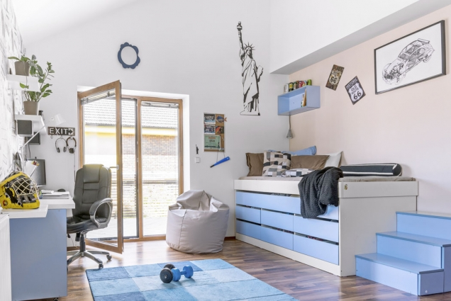 Vyvýšená postel přístupná poschůdkách má vesvých útrobách úložné zásuvky.