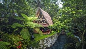 Bambusový domek sikonickými okny, svýhledem naprotitekoucí řeku. Vnaprostém soukromí aklidu přírody.