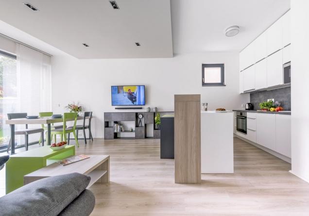 Přízemí domu tvoří velká místnost, která slouží jako kuchyň sbarovým posezením, jídelna aobývací pokoj.