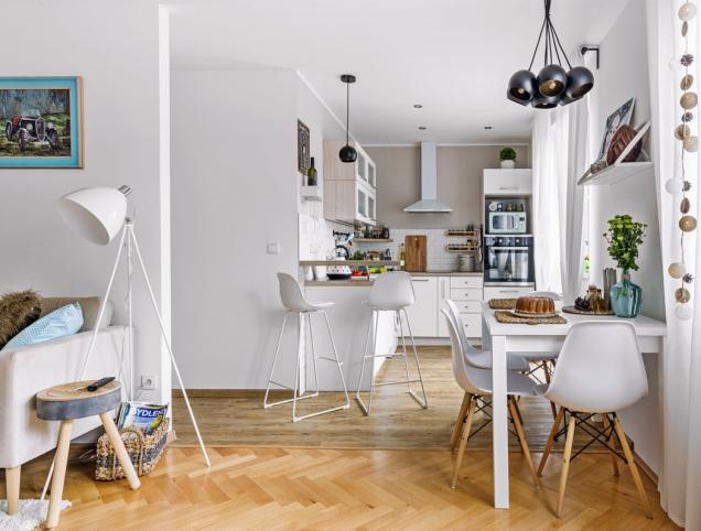 Pojícím prvkem kuchyně aobývacího pokoje je jídelna sbílým stolem adesignovými židlemi. Zajímavým detailem jsou závěsná svítidla zakoupená vpražské prodejně Elusia.