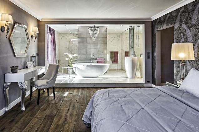 Zlatým hřebem interiéru je ložnice. Dřevěná podlaha skrásnou rustikální strukturou rafinovaně přechází vmramorový sokl, naněmž je jako nadivadelní scéně umístěna otevřená koupelna vhlavní roli snádherně tvarovanou solitérní vanou.