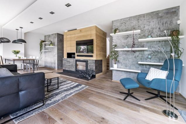 Dominantou obytného prostoru vpřízemí je středový modul obložený dubovou dýhou. Nabízí úložné prostory, krb imísto pro TV adalší audio.