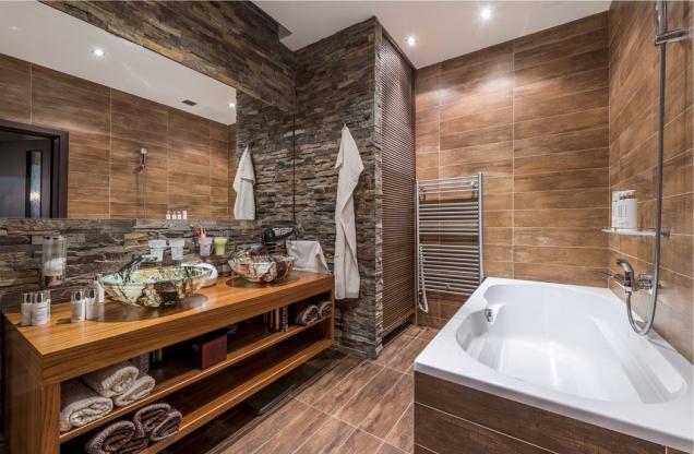 Koupelna je chloubou majitelky bytu. Zmalé neútulné místnůstky se zašlými bleděmodrými kachlíky vznikla oáza klidu arelaxace. Za dřevěnou roletou se ukrývá pračka, nalevo od umyvadel je sprchový kout typu walk-in.