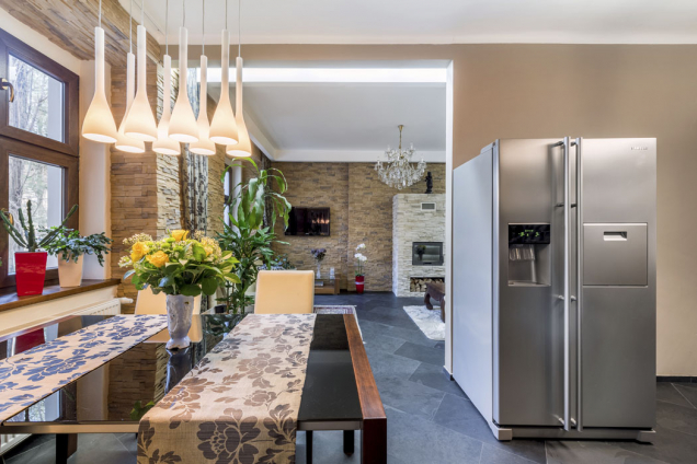 Kuchyň (od lednice vpravo) je přes jídelní kout propojena sobývací částí. Vše sjednocuje kamenná dlažba antracitové barvy dovezená na objednávku až zBrazílie. Její barva ladí skuchyňskou linkou iněkterými doplňky.
