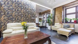 Výraznému obkladu zkamene na jedné ze stěn směle konkuruje textilní tapeta skvětinovým vzorem, která nachází oporu  vdekoru závěsů.