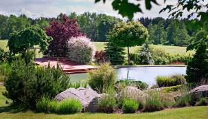 Bazén nemá klasický tvar, ale organické křivky, aby lépe zapadal dozahrady. Vpozadí je vidět respekt kestávajícím výsadbám aokolní přírodě. Dřeviny se vevětšině případů nekácely, plně se využívá vlastností travin atrvalek, které se zapojují dosmíšených záhonů.