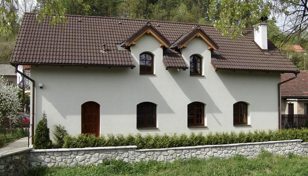 """9. Barvy, štuky, detaily: Dům, který na první pohled vykazuje všechny prvky tradiční architektury, dobře zapadá do venkovské výstavby. V detailu postrádá stavba propracované detaily. Jednobarevná hladká omítka spolu s tmavými """"vysleplými"""" okny působí smutně. Naštěstí lze poměrně jednoduše tuto situaci změnit."""