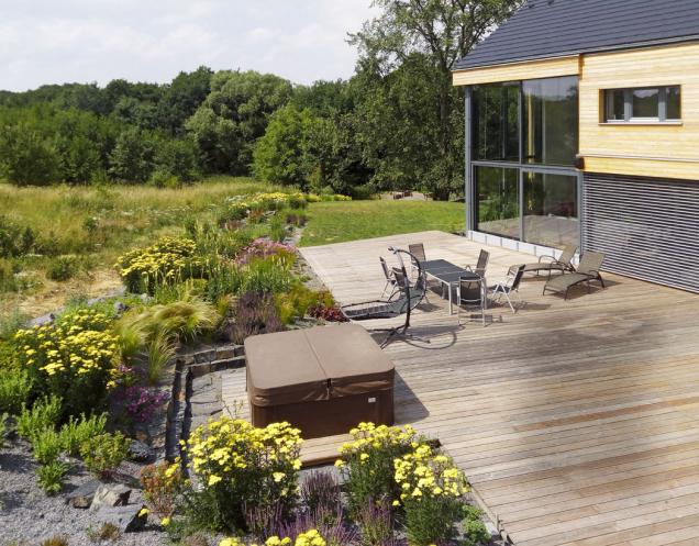 Zahrada vtěsné blízkosti rodinného domu vytváří rozšířený obytný prostor smožností aktivního vyžití na terase, střešní zahradě ina pobytovém trávníku. Převažuje osázení stepními a lesními druhy vnávaznosti na okolní přírodu sdominantním vysokým jilmem.