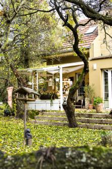 Jako útulný pokojík zařízená, proti dešti apadajícímu listí chráněná terasa udomu láká ke klidnému rozjímání.