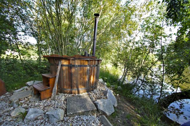 Koupací sud je umístěn na pevnině za chatkou. Vodu vněm ohřívají kamínka, dřevěné pádlo slouží kpromíchání teplé achladnější vody.