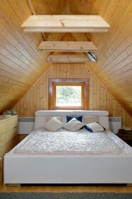 Do podkroví vedou schody přímo z obytné místnosti. Je tu místo přesně na manželskou postel a komodu, děti spí na protější straně.