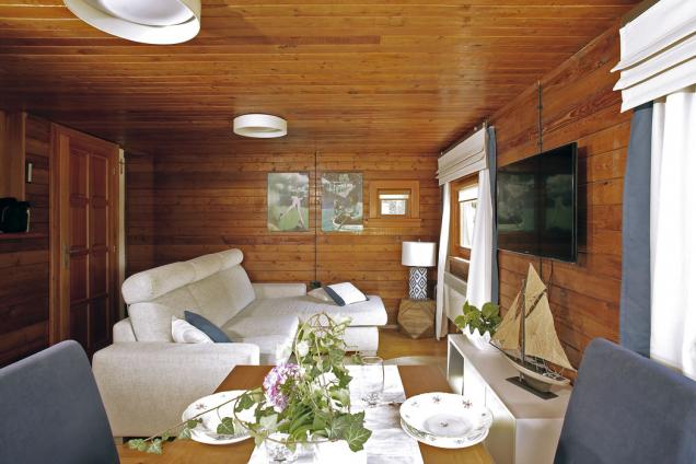 Modřínové dřevo vládne jak exteriéru, tak interiéru, kde pokrývá všechny povrchy. Jeho načervenalý odstín působí příjemně teple a struktura dodává stěnám členitost.