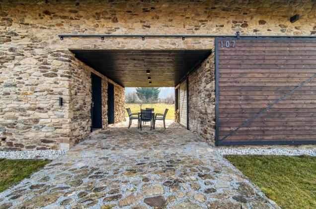 """Volný """"průjezd"""" domem slouží především jako krytá terasa k venkovnímu posezení. Z obou stran jej lze uzavřít posuvnými dřevěnými vraty a vytvořit tak zcela chráněný prostor"""