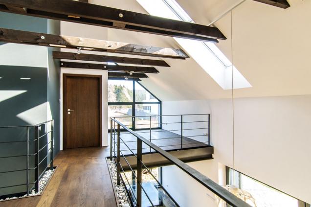 Vnitřní uspořádání je zcela moderní. Dřevěný trámový strop a galerie nad společnou obývací částí jako by se volně vznášely v prostoru. Střešními okny i oknem ve štítě sem proniká hodně světla.