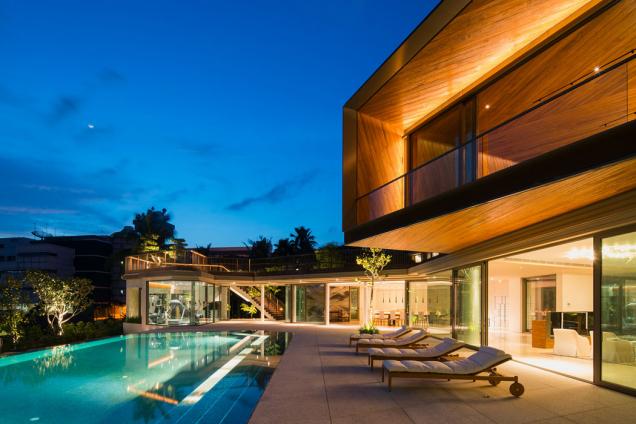 """Architekti soukromé rezidence """"House X"""" vSingapuru si vrámci fasády pohráli sprotiklady soukromí a otevřenosti. Zatímco směrem do ulice je dům diskrétně uzavřený, na jihozápadní straně se budova otvírá a poskytuje fascinující výhledy na přírodní panoráma i zázemí domu. Aby si obyvatelé domu mohli užít přírodu a podnebí a zároveň vinteriérech měli příjemné klima, vytvořily prosklenou fasádu posuvné hliníkové systémy Schüco. (Zdroj: Schüco, autor fotografie: Khoo Guojie, Singapore)"""