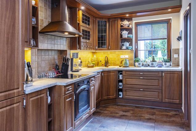 Okno vkuchyni nad kuchyňskou linkou vetvaru písmene L zásobuje místnost přirozeným denním světlem.