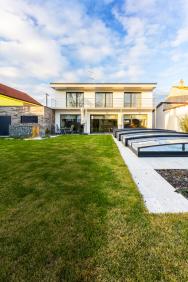 Když majitel stavební developerské společnosti objevil vevzdálenosti dvou kilometrů odsvého bydliště zajímavou parcelu v proluce řadových domů, neodolal arozhodl se postavit zde své rodinné sídlo vpasivním standardu.