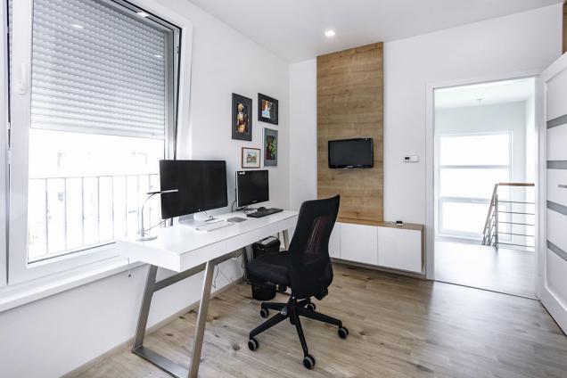 V jednom ze tří pokojů v patře je umístěna domácí pracovna. Předokenní rolety dokáží účinně bránit přehřívání a udržet v domě i v horkém létě příjemné klima.