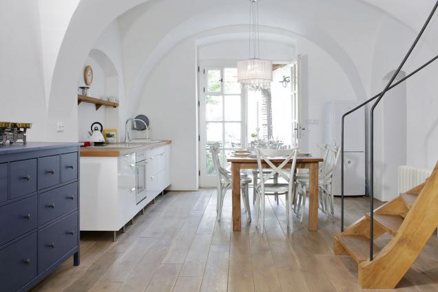 Z kuchyně se vychází novým francouzským oknem na malý dvorek. Nízkou kuchyňskou linku doplňuje police umístěná v nice, vpravo je vidět  schodiště na místě původní černé kuchyně.