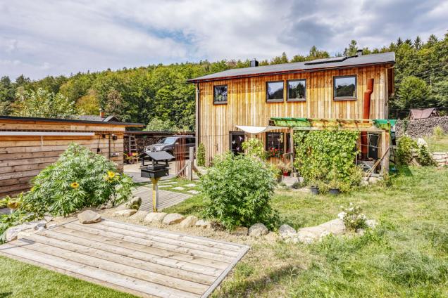 Pohled ze zahrady na dům aterasu. Na pravé straně je vidět jednopodlažní dřevostavbu se skladem zahradní techniky aodpočinkovou místností se saunou.