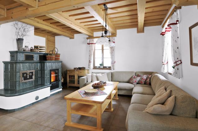 Obývací pokoj vtradičním duchu doplňují stylová kamna, ale najdete tu iplazmovou televizi, domácí kino ahi-fi soupravu.