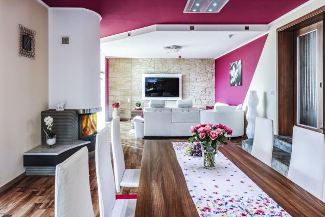 Vinteriéru majitelé domu zkombinovali výrazné barvy spřírodními materiály ajejich imitacemi, napodlahy zvolili laminát sdezénem dřeva, obklad čelní stěny vobýváku napodobuje lomový kámen.